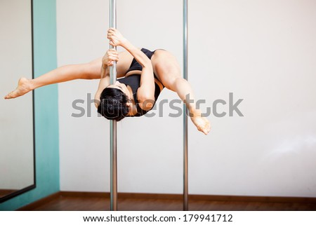 Strong Latin woman holding a pose during a pole dancing class at a gym - stock photo