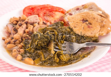 Strong light from upper right on collard greens seasoned with salt pork and red onions and black-eyed peas with chunks of spam.  Pink gingham tablecloth emphasizes country kitchen feel. - stock photo