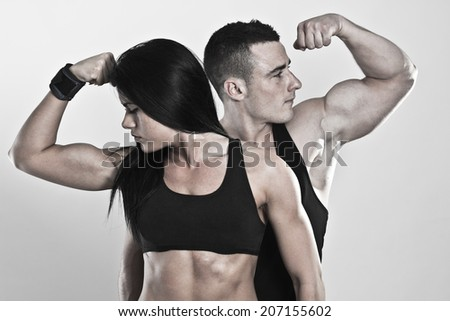 Strong man and a woman posing on a black background  - stock photo