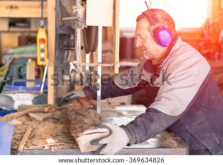 Strong man carpenter using table saw for cutting wood at workshop - Woodworker working hard in Switzerland mountains - Industrial work concept - Soft warm filtered look with artificial sunlight - stock photo