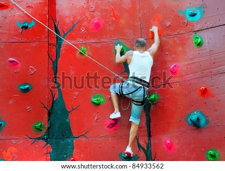 strong man climbing on a climbing wall training in insurance