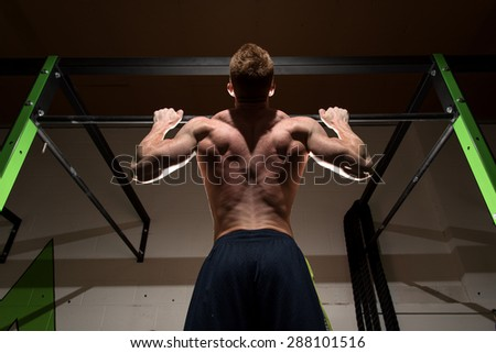 Strong man doing pull up in dramatic light. Dramatic light gives a motivated, focused, determined feel to the image. - stock photo