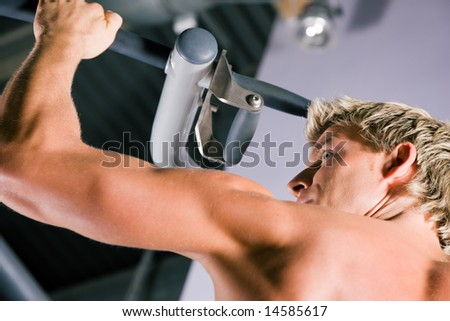 Strong man doing pull-ups on a machine in the gym