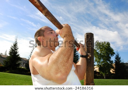 Strong Man Doing Pullups in the Park on a Sunny Day - stock photo