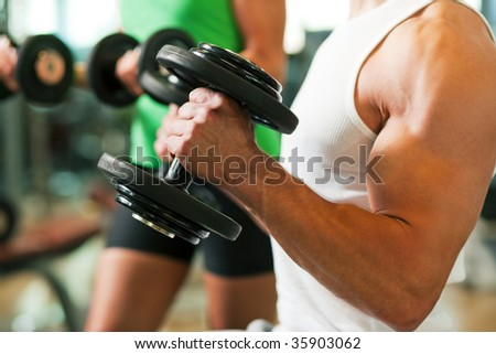 Strong man exercising with dumbbells in a gym, in the background a woman also lifting weights; focus on hands - stock photo