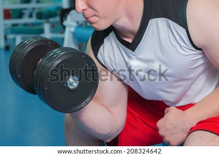 Strong man holding a dumbbell in the gym. Man doing exercise with dumbbell. Gym, weights, muscles, sports, strength. - The concept of a healthy lifestyle. Article about the sport and health.