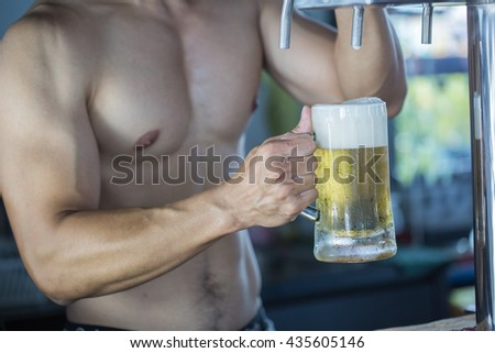 Strong Man is pouring draught beer from tap, selective focus point, concept balance life - stock photo