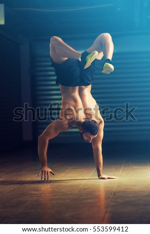 Strong man is walking on hands upside down.