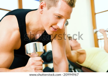 Strong man lifting dumbbells in a gym, a woman training on a machine in the background - stock photo