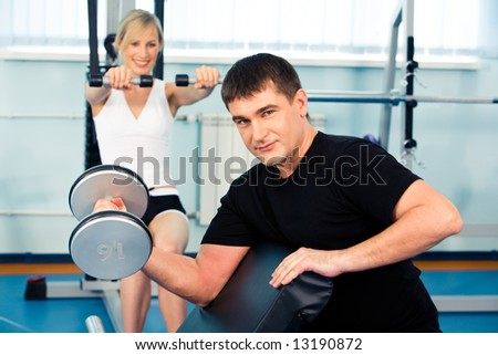 Strong man lifting weight on the background of woman with dumbbells