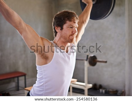 Strong man looking fiercely determined while lifting heavy weights in a private gym - stock photo