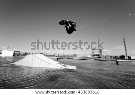 strong man making trick in jump time with wakeboard on sky background. black and white concept. - stock photo