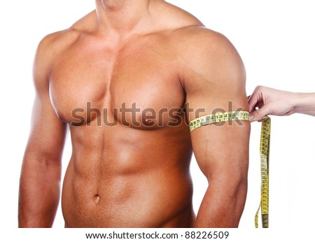 Strong man measuring his arm, isolated on white - stock photo