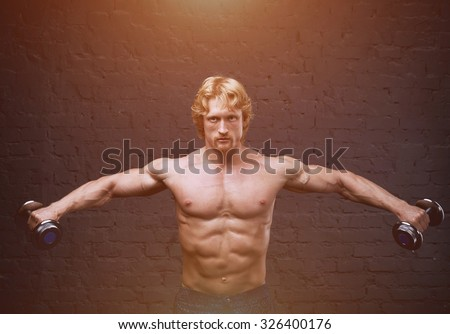 Strong man raises heavy dumbbells in his hands. Advertising fitness center or gym. He strained all the muscles of the body. Muscular man on dark background. He trains the muscles and lifts weights. - stock photo