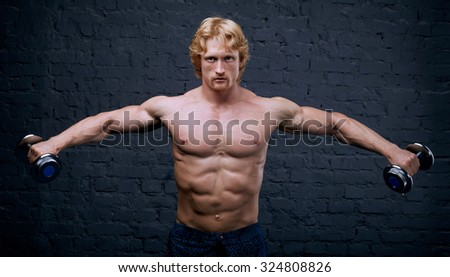 Strong man raises heavy dumbbells in his hands. He strained all the muscles of the body. Muscular man on dark background. He trains the muscles and lifts weights. Advertising fitness center or gym.
