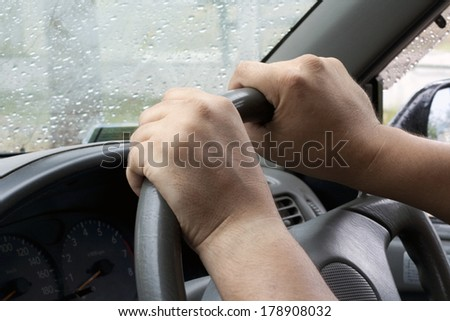 Strong man's hands on steering wheel