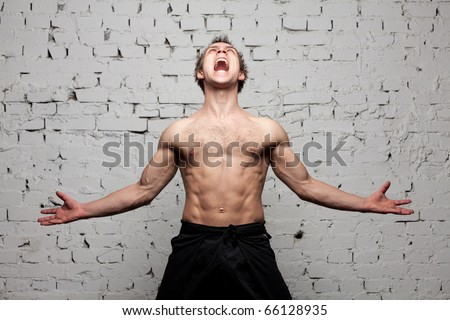 strong man  shouting and roaring against a brick wall - stock photo