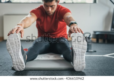 strong man stretching legs before gym workout. Fitness sporty male athlete on floor mat and towel warming up. - stock photo