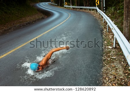 Strong Man Swim On Asphalt Road - stock photo