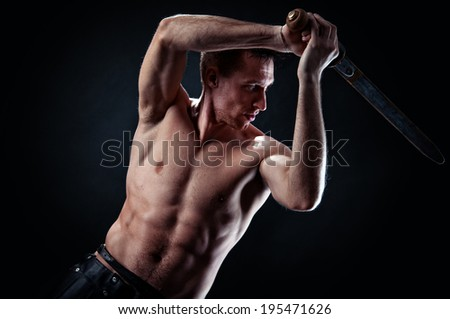 Strong man training with ancient sword the black background - stock photo