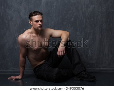 Strong man with a naked torso in black pants and boots sitting on a wooden floor in the studio