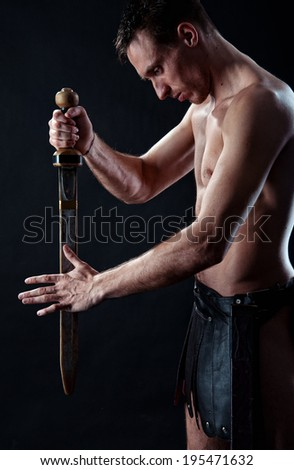 Strong man with ancient sword and  armor on the black background - stock photo