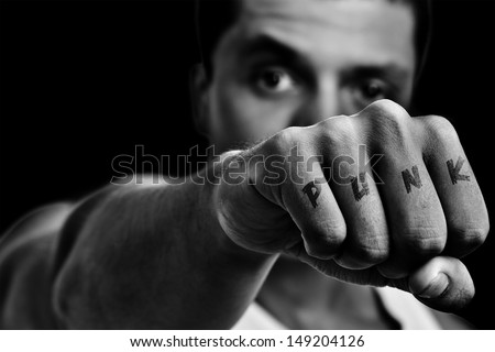 Strong man with punk attitude and a tattoo written punk in his punch. In Black and White.