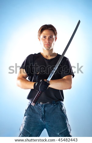 Strong man with samurai sword. On soft blue background. - stock photo