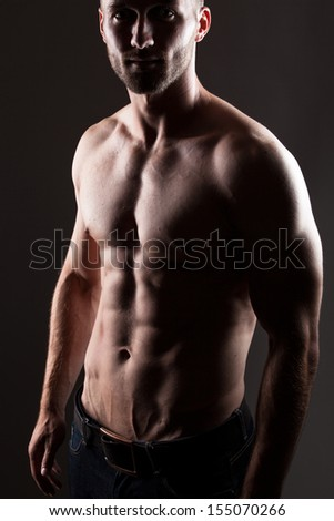 Strong man with strong abdominal muscles in low light