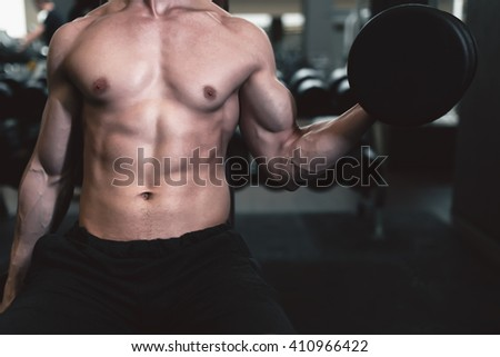 Strong man working at gym fitness club