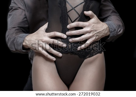 Strong mand hands holding woman hip, sensual lovers in dark, closeup - stock photo