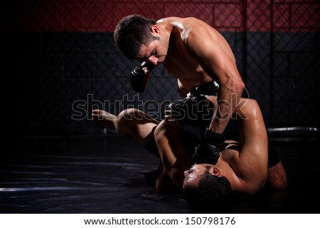 Strong MMA fighter holding his rival down and throwing punches at him during a fight. With plenty of copy space - stock photo