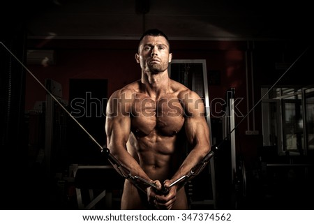 Strong muscular body builder  in the gym