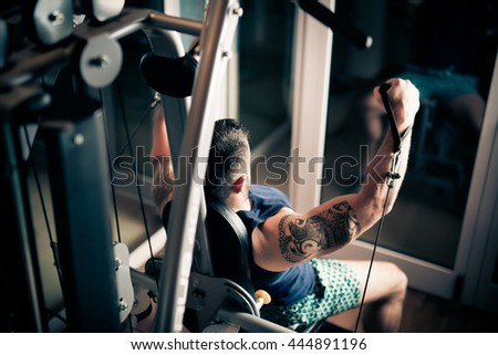 Strong muscular bodybuilder doing exercise on rowing machine in the gym. Part of fitness body. Sports and fitness. Fitness man in the gym. Strong man at the gym lifting weights.Low key - stock photo