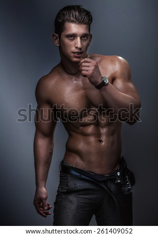 Strong muscular handsome man posing in studio naked. - stock photo