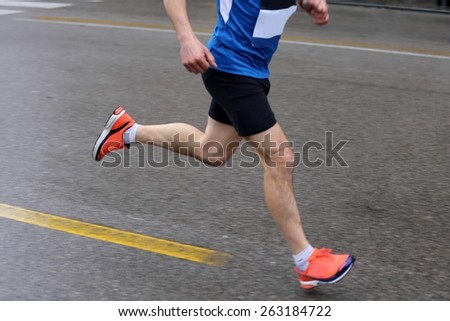 strong muscular legs of the athlete during the road race with rain, motion blur