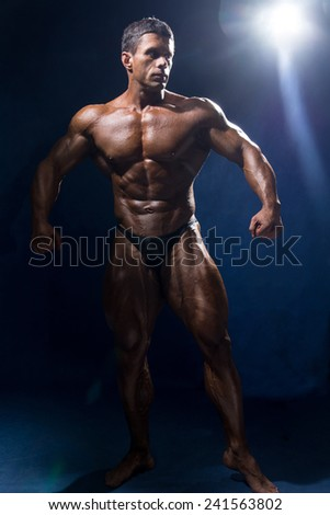 Strong muscular man bodybuilder in full growth. sportsman fitness - stock photo
