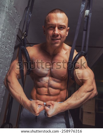 Strong muscular man bodybuilder poses and shows his abs and bicepses - stock photo