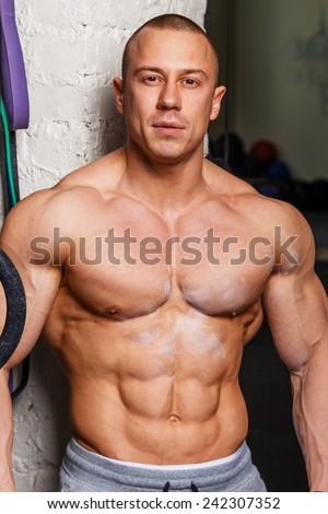 Strong muscular man bodybuilder poses and shows his muscles - stock photo