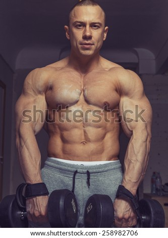 Strong muscular man bodybuilder shows his muscles holding dumbbells - stock photo