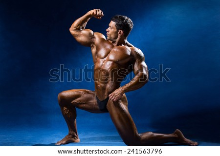 Strong muscular man bodybuilder shows his muscles. Sportsman fitness on a blue background - stock photo