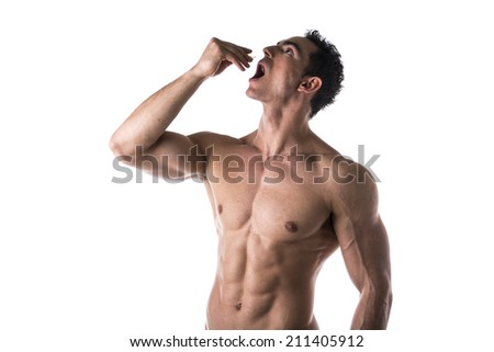 Strong muscular man taking diet supplements or pharmaceutical medication standing shirtless with his mouth open and head tilted back as he drops a pill from his hand or places something in his mouth - stock photo