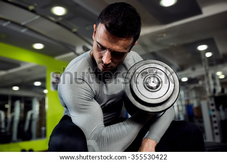 Strong powerful male exercise biceps with weight - stock photo