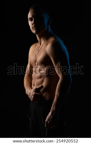 strong sexy man on a black background - stock photo