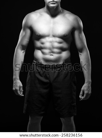 Strong sexy powerful body with naked torso and black shorts, isolated on black background, black-and-white - stock photo