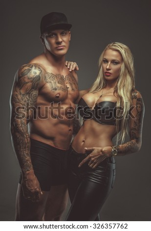 Strong shirtless tattooed man in a cap and blond sporty woman in black bra isolated on grey background.