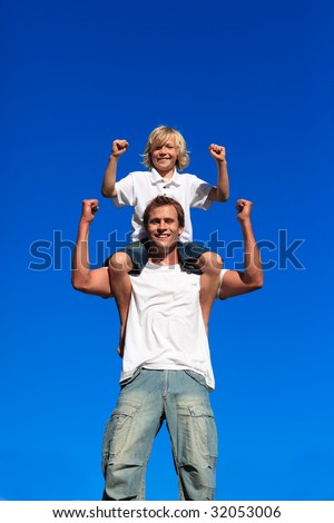 Strong son sitting on his father's shoulders against blue sky - stock photo