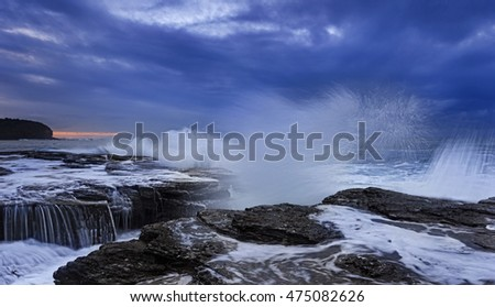 Strong splash of approaching ocean wave eroding sandstone rocks of Australia pacific shore near Sydney. Stormy sunrise weather near Narrabeen head rocks.