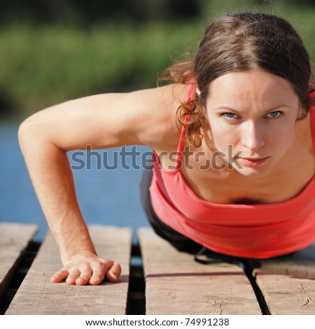 Strong sporty female doing push-ups outdoors - stock photo