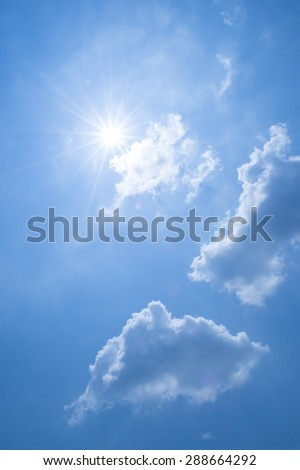 Strong sun and clouds on blue sky.